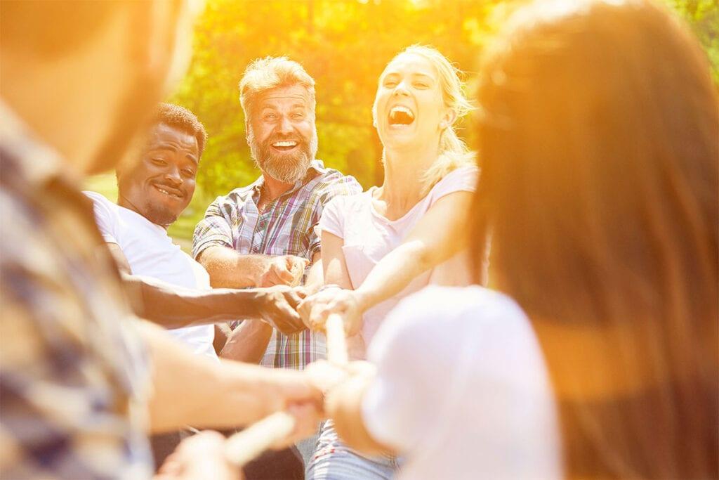 Glade mennesker hygger sig med tovtrækning til et firmaarrangement