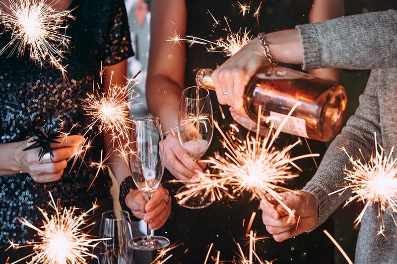 Kollegaer til firmafest. Holder glas og stjernekastere i hånden.