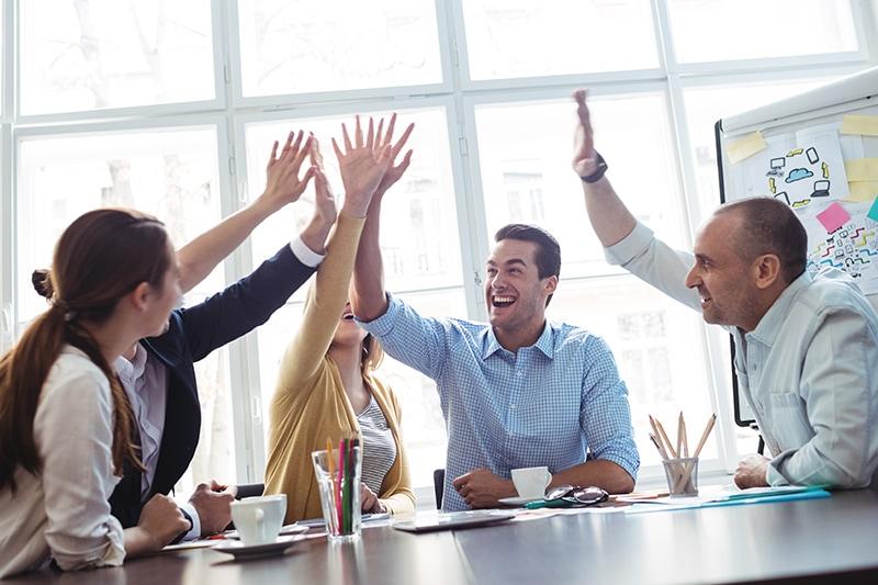 Kollegaer giver high five til kickoff møde.
