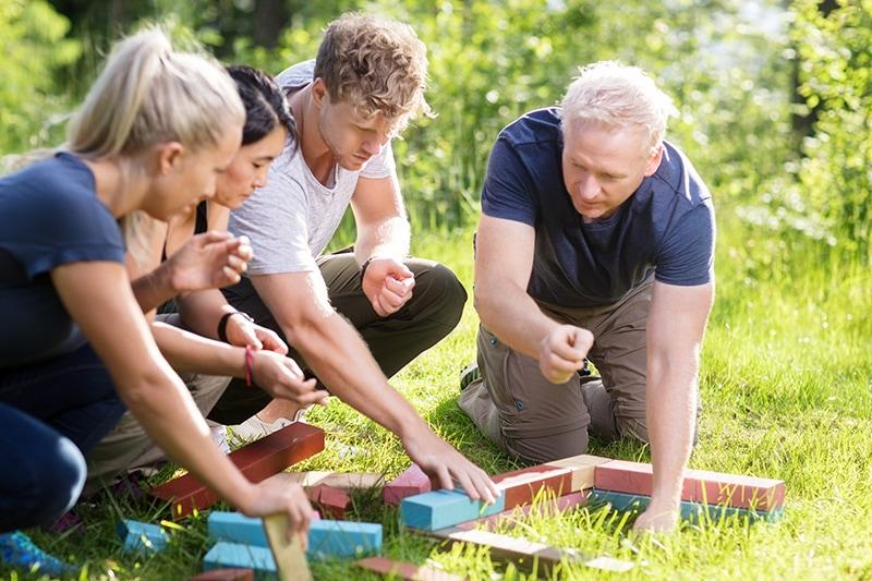Mennesker samarbejder om teambuilding-øvelse.